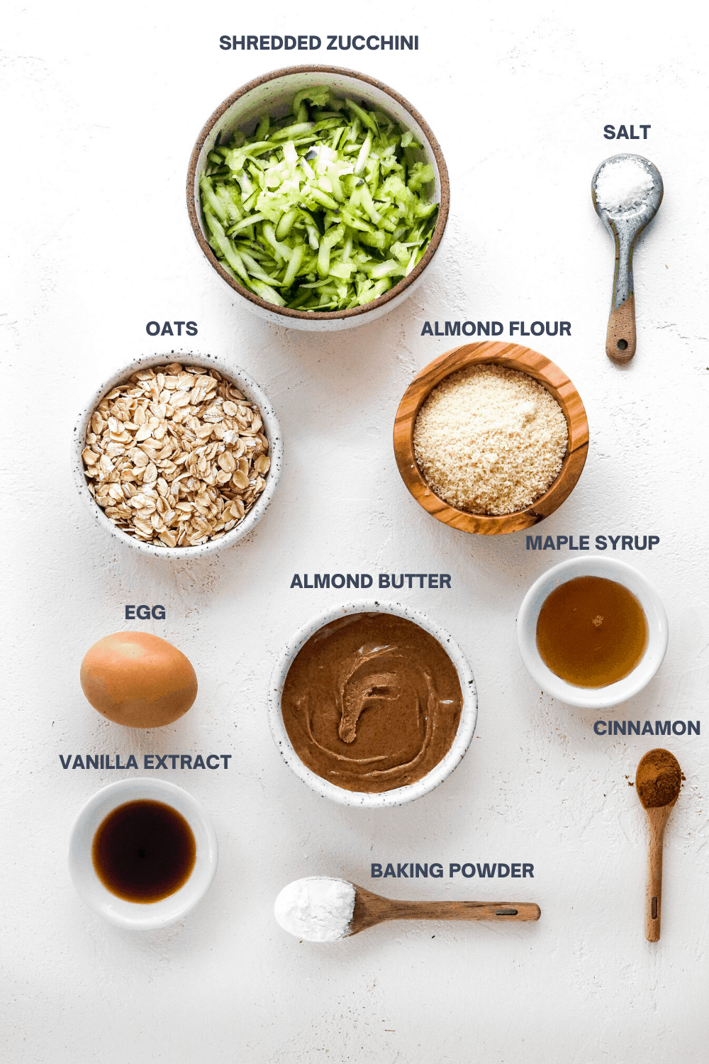 Round bowl filled with grated zucchini with a bowl of oats, bowl of almond butter, egg, maple syrup and a spoon of salt and cinnamon around it on a white surface.