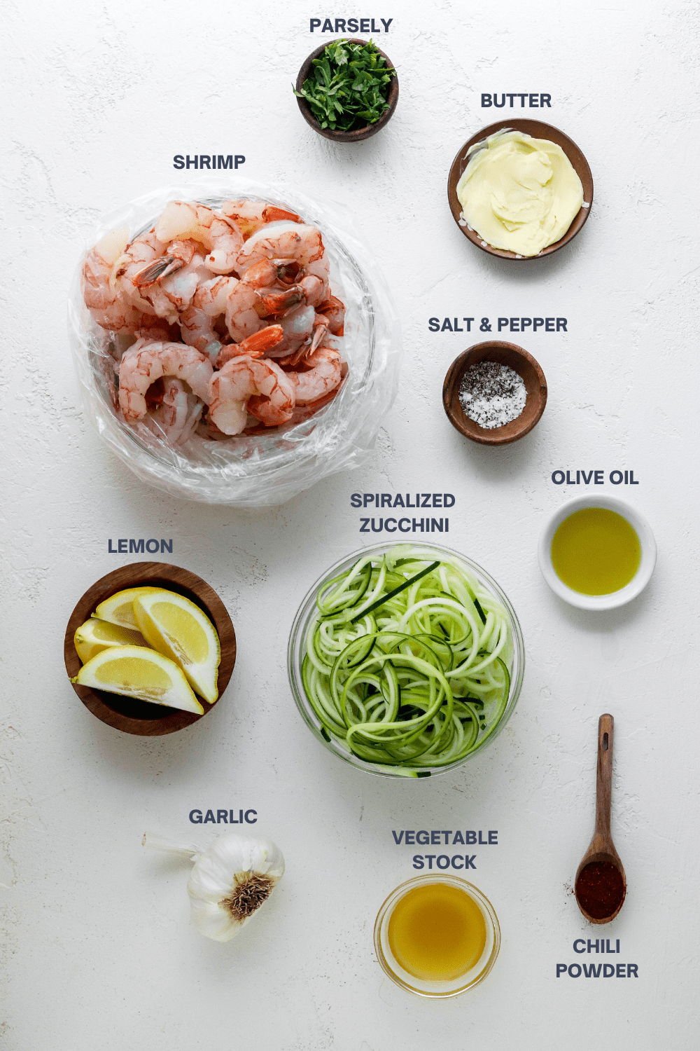 Bowl of shrimp with a wooden bowl of parsley, plate of butter, bowl of salt and pepper around it with a bowl of spiralled zucchini noodles, wooden bowl of lemon wedges, small shite bowl of olive oil and a wooden spoon with spices in front of it with labels on  top of each item.