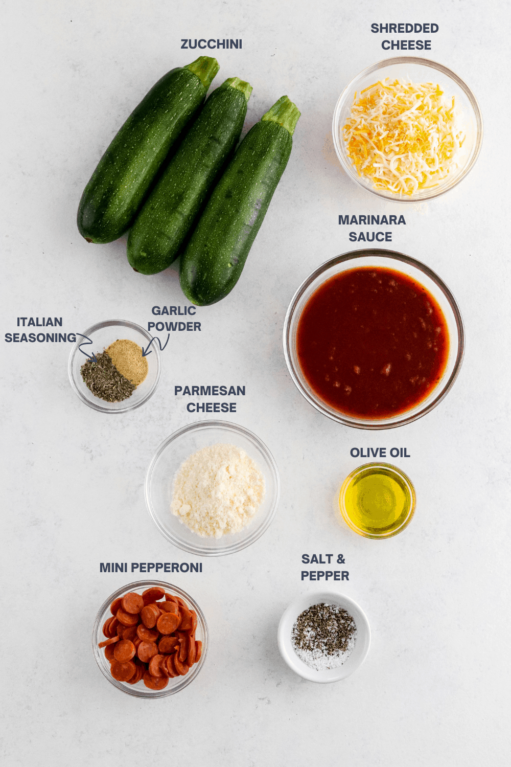 Whole zucchini, bowl of shredded cheese, bowl of red sauce, bowl of seasoning, bowl of parmesan cheese, bowl of olive oil, Bol of mini pepperoni and a bowl of salt and pepper on a white surface.