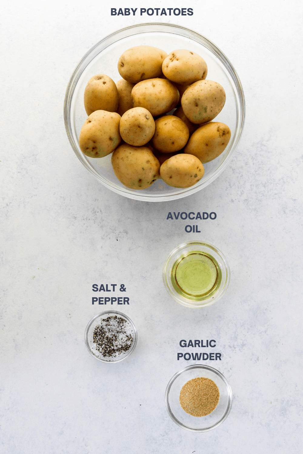 Round glass bowl filled with golden baby potatoes with a small glass bowl oil, a bowl if salt and pepper and a bowl of garlic powder in front of it.