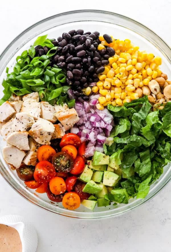 Large round glass bowl with lettuce, diced chicken, corn, black beans sliced tomatoes, red onion and diced avocado separated in the bowl.