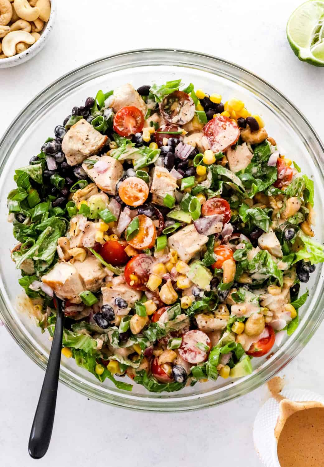 Glass round mixing bowl filled with green romaine lettuce, corn, sliced tomatoes, black beans and diced cooked chicken topped with a drizzled with a creamy pale orange dressing with a black spoon in the bowl.