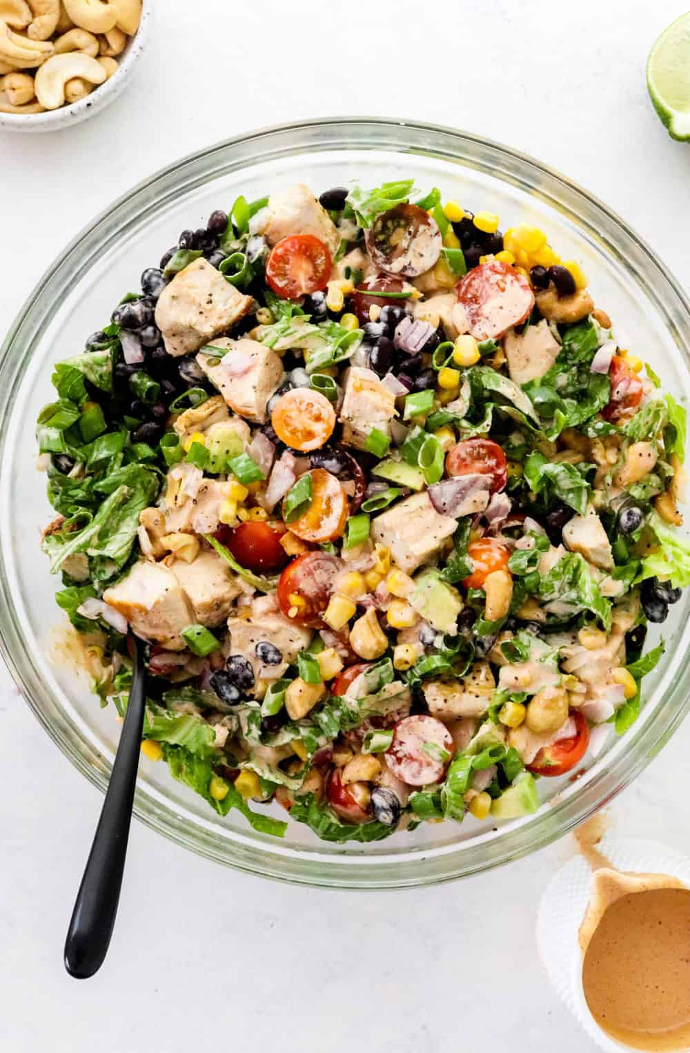 Round glass bowl filled with creamy bbq chicken salad over torn green lettuce with a black spoon in the bowl and a white pouring container with orange dressing in front of it.