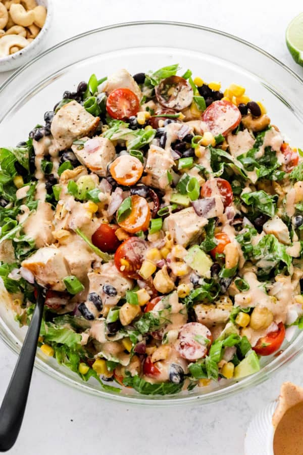 Close up of a creamy bbq chicken salad in a glass bowl with a black spoon in the salad