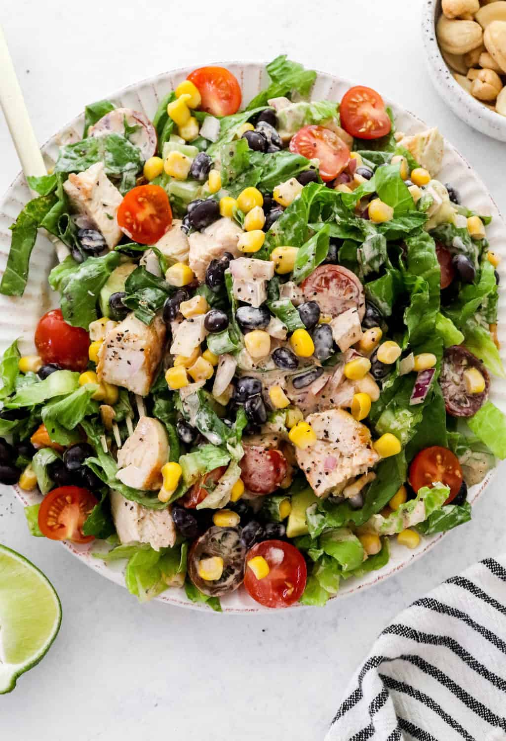 Pile of a mixed chicken salad over romaine lettuce with black beans and corn in it on a round white plate with a gold fork in it with a bowl of cashews behind it.