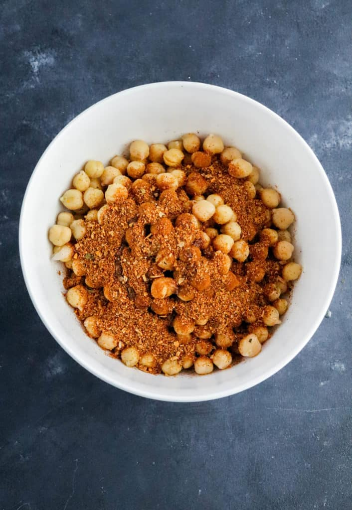 Round white bowl filling with chickpeas with brown seasoning on top of them on a dark blue surface