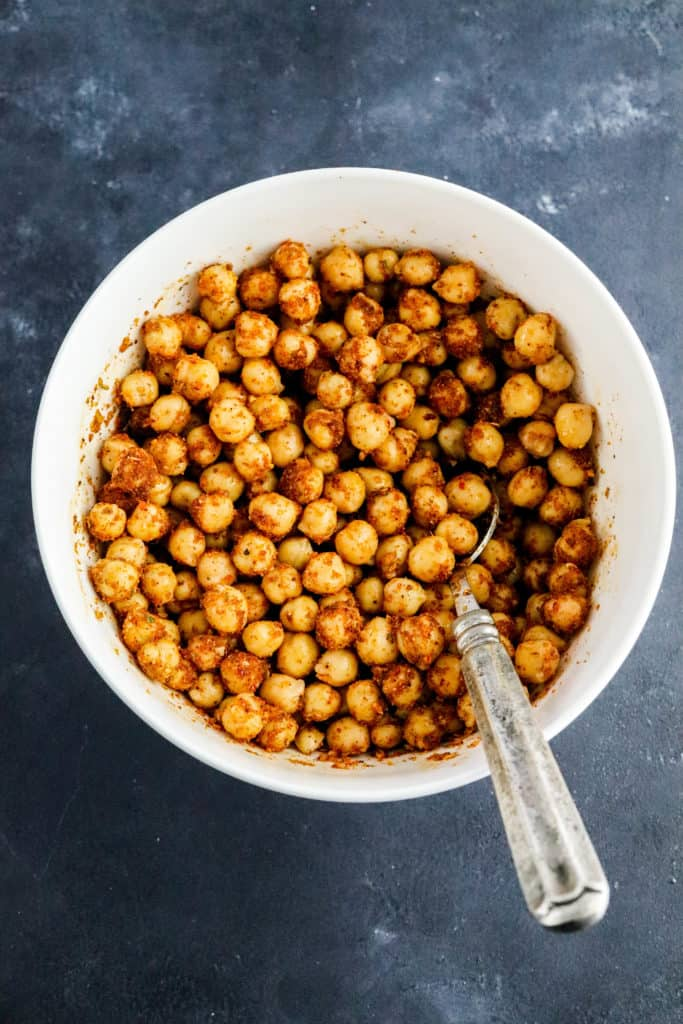 Mixed up seasoned chickpeas in a white bowl with a silver spoon in the bowl on a dark surface.