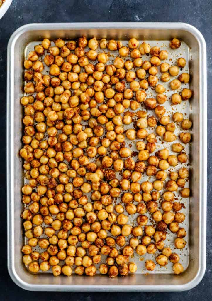 Silver pan with raw, seasoned chickpeas spread our on it.