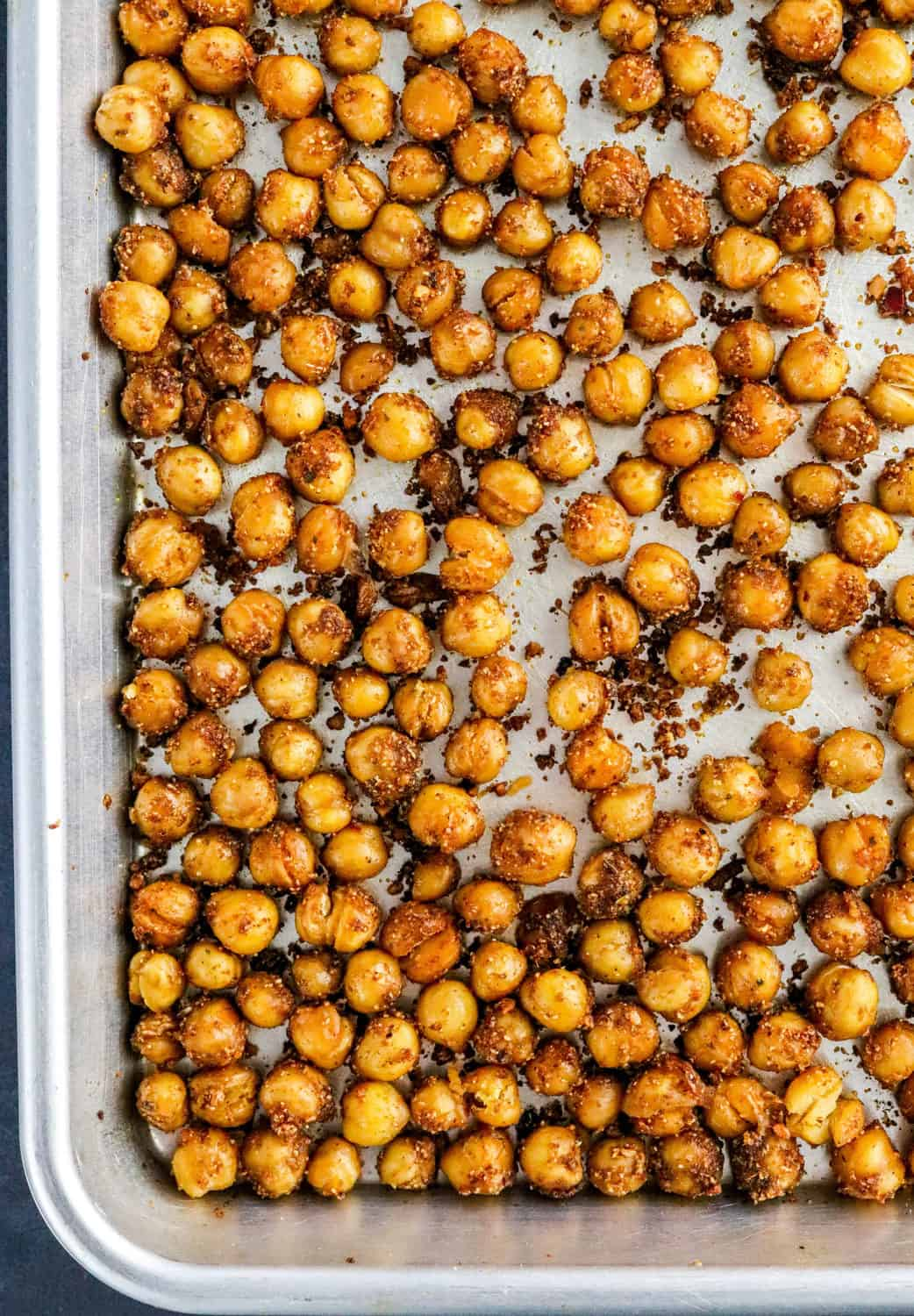 Close up of super crispy brown chickpeas spread out on a baking sheet