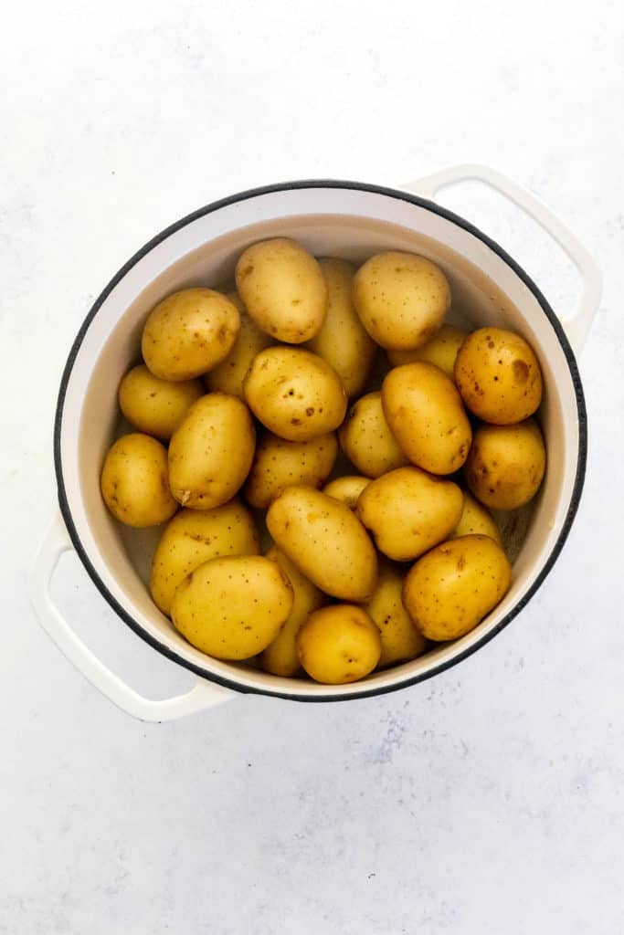 Round white pot filled with baby golden potatoes covered in water on a white surface