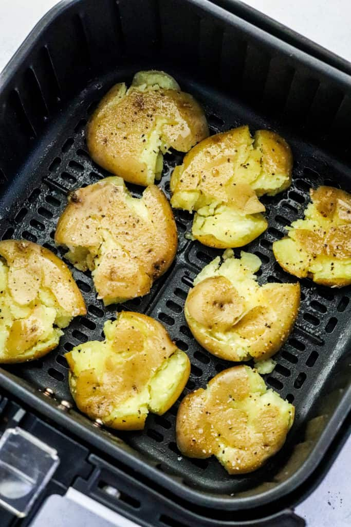 Smashed baby potatoes in an air fryer basket