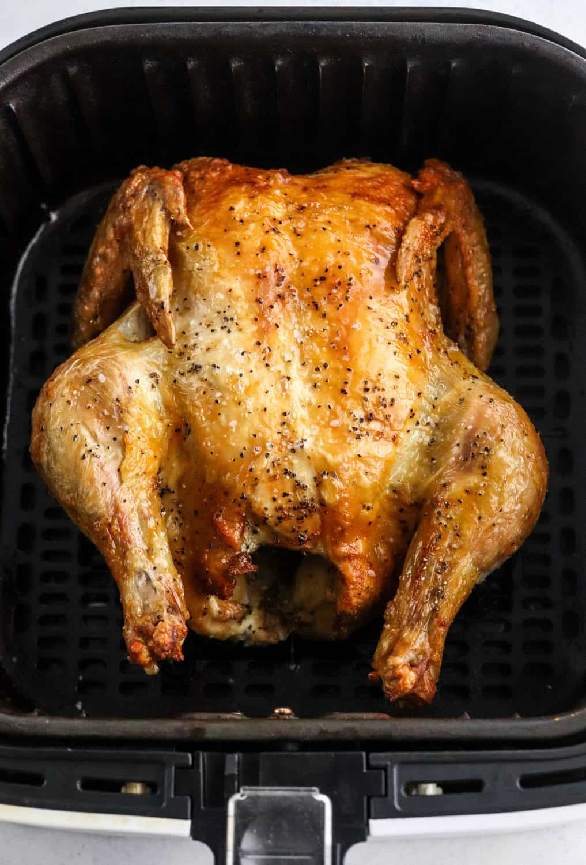 Whole crispy chicken in an air fryer basket