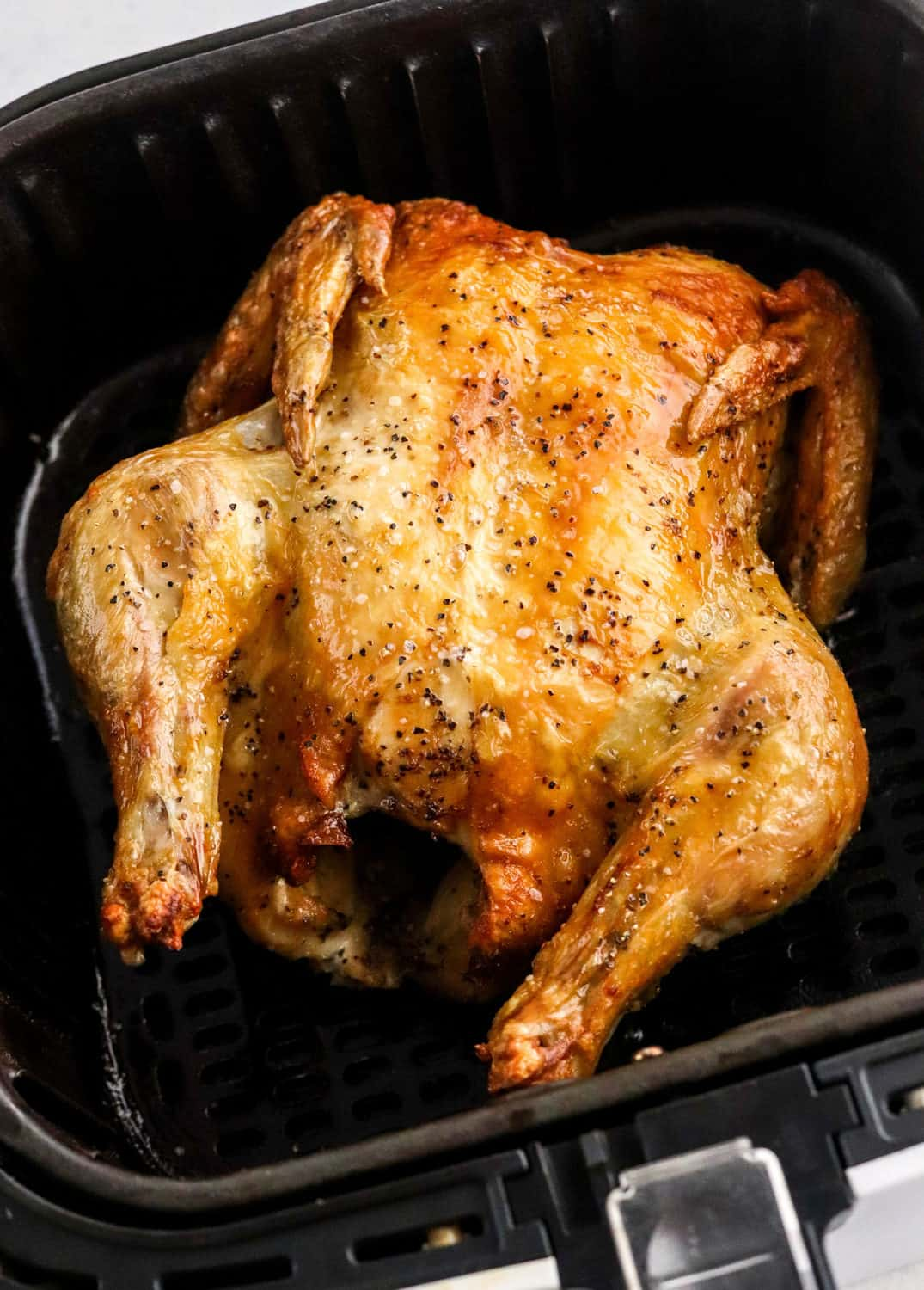 A whole chicken cooked with crispy skin in the air fryer.