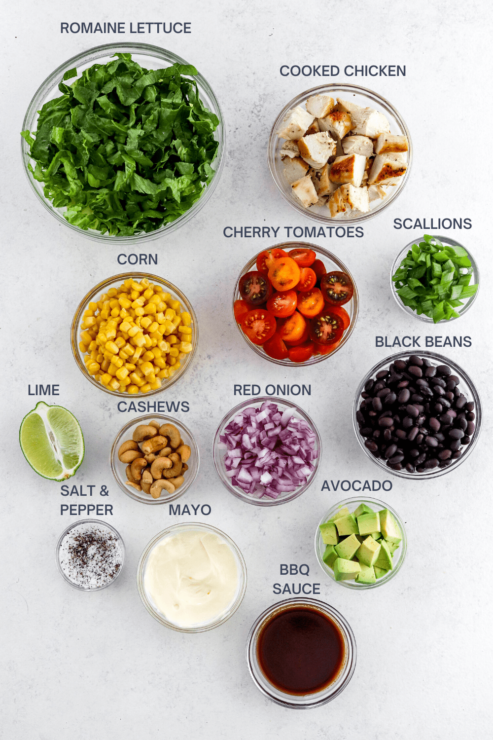 Bowl of green lettuce, bowl of diced chicken, bowl of corn, bowl of sliced tomatoes, bowl of scallions, bowl of black beans. bowl if nuts, bowl of diced red onion, bowl if diced avocado, lime sliced in half, bowl of mayo and a bowl of bbq sauce on a white surface with labels above each bowl.