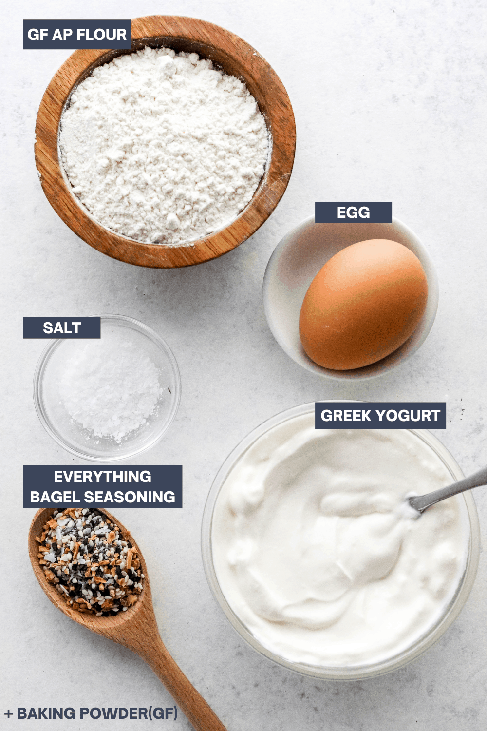 Round wooden bowl filled with white flour, brown egg, bowl of salt, bowl of Greek yogurt and a wooden spoon filled with bagel seasoning on a white board with blue specs in it.