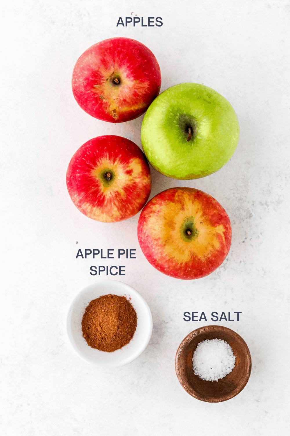 3 red apples and 1 green apple on a white surface with a small white bowl of apple pie spice and a brown bowl filled with sea salt in front of it.