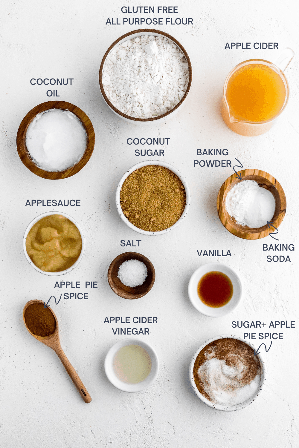 Round brown bowl with flour in it with a glass pitcher of cider and a brown bowl of coconut oil next to it with bowls with coconut sugar, baking powder, baking soda, salt, vanilla. apple cider vinegar and sugar in front of it.