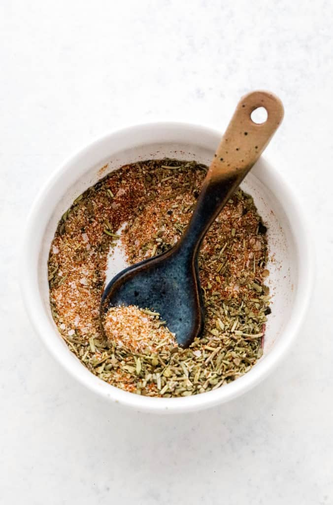 Spice blend in a round white bowl with a small, blue spoon in it