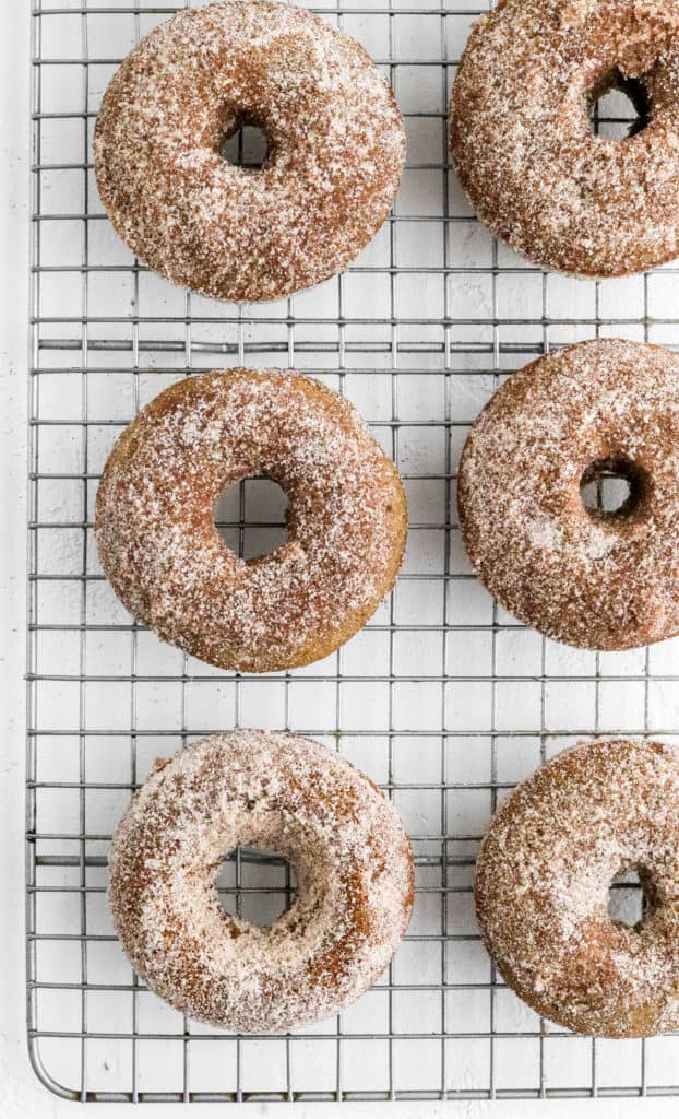 Cinnamon sugar coated donuts on a wire rack