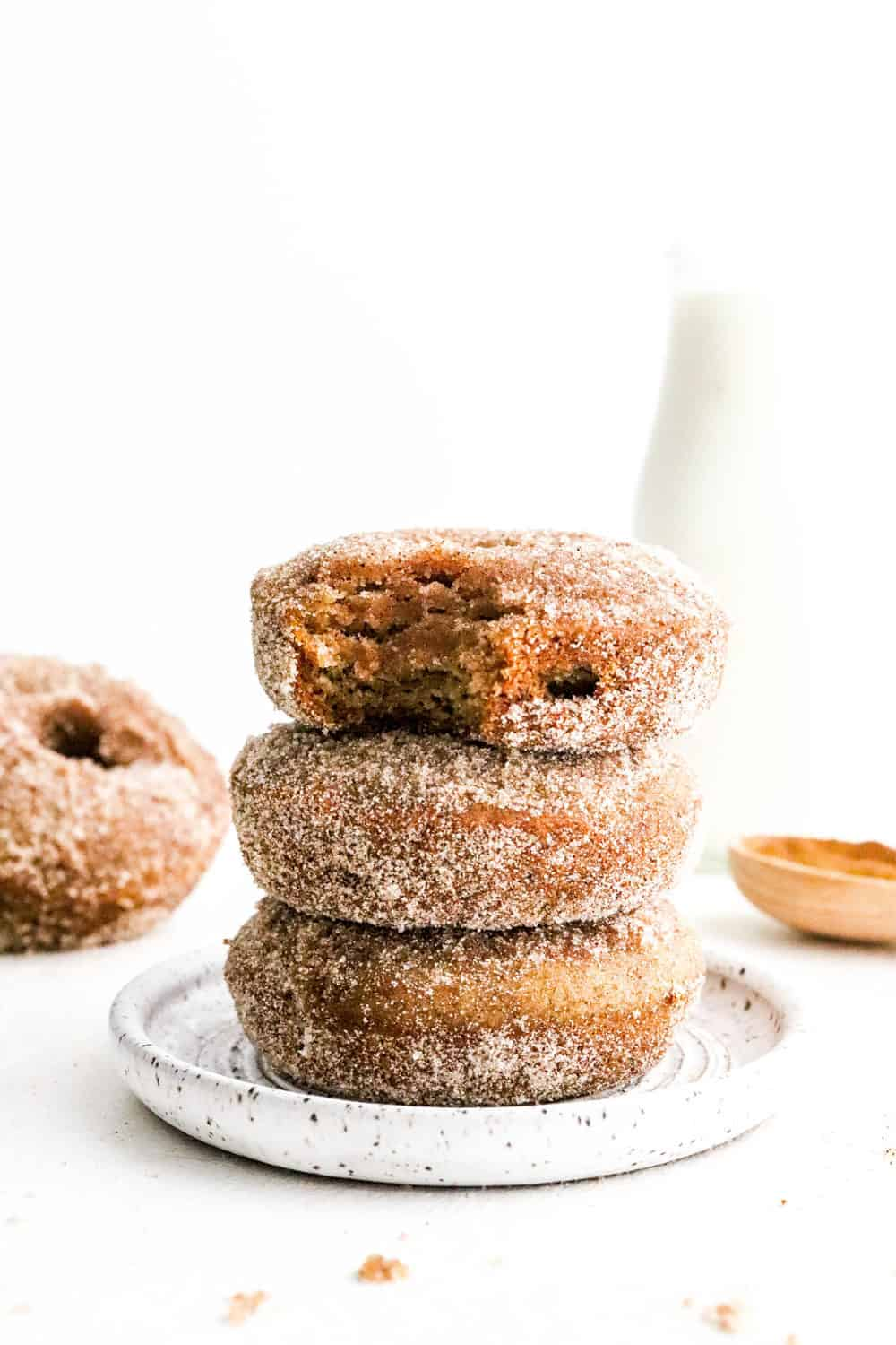 Stack of 3 sugar coating brown apple donuts on a round white plate with more donuts behind it with a bit taken out of one of the donuts.