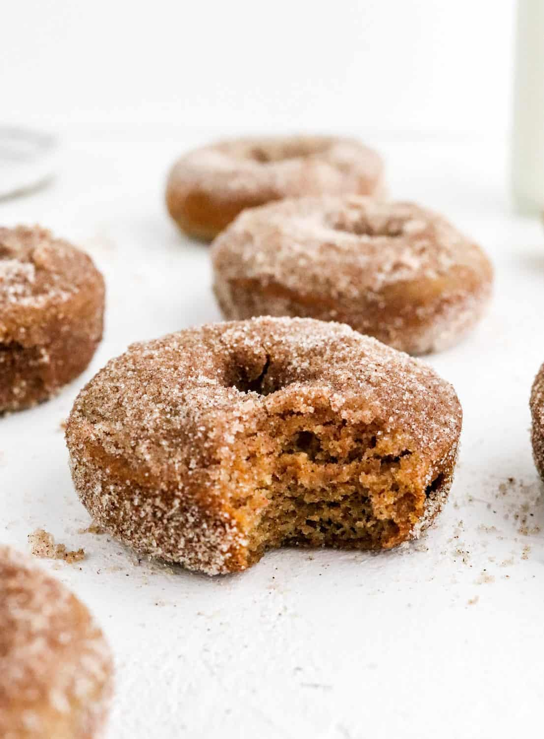 A few brown donuts with brown sugar on them with a bite taken out of one of the donuts on a white surface.