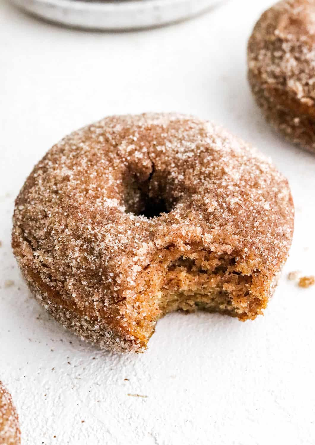 A single apple cider donut on a white surface with another donut next to it.