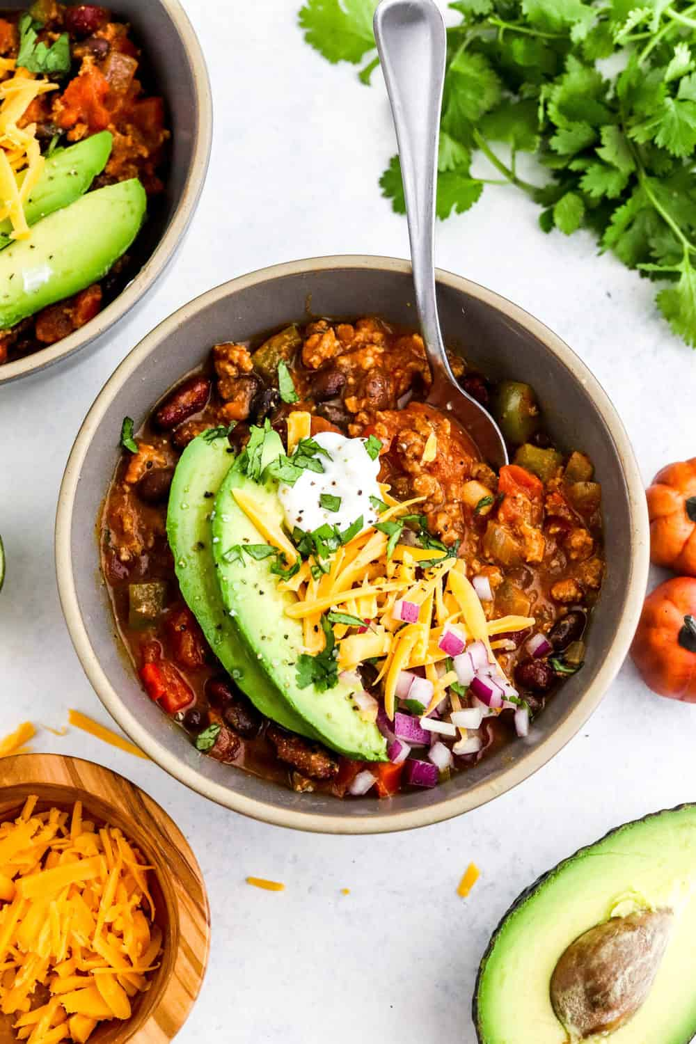 Round dark grey bowl filled with chili with a spoon in it with sliced avocado, shredded cheese and onions on top with another bowl of chili and bunch of cilantro behind it.