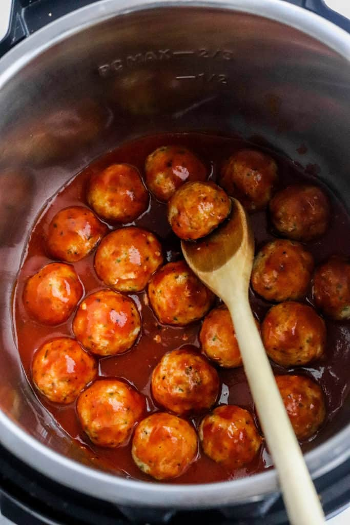 Cooked meatballs in BBQ sauce in a crock pot with a wooden spoon in the pot