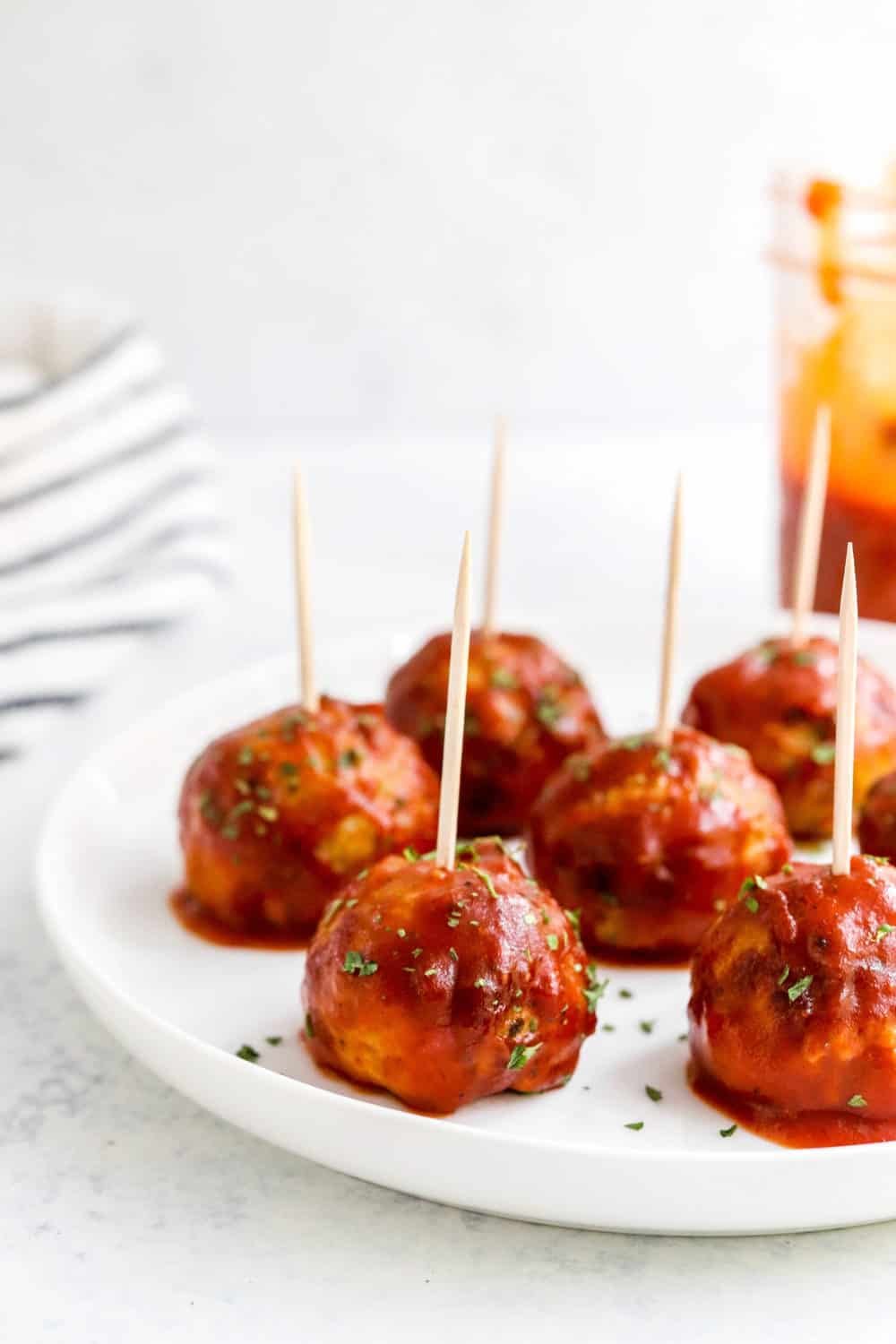 Round white plate with bbq meatballs with toothpicks stuck in them spread onto the plate with a striped towel and jar of bbq sauce behind it.