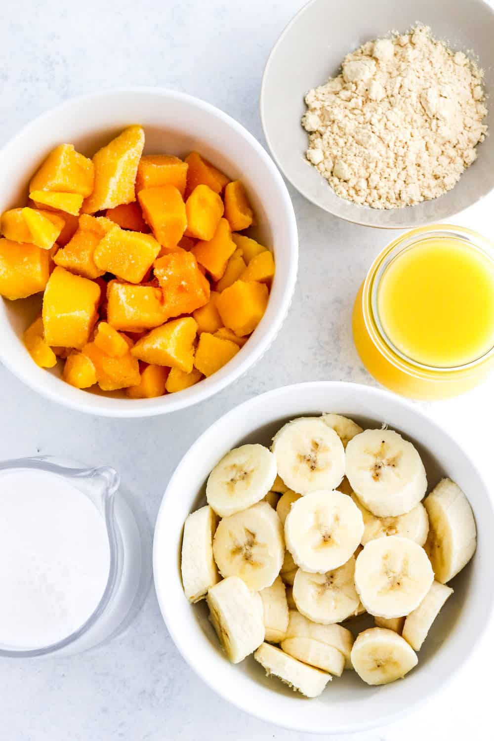 White round bowl filled with frozen mango pieces, with a bowl of protein powder and glass of orange juice next to it and a round white bowl filled with cut bananas in front of it.