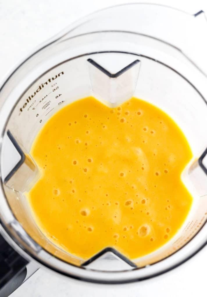 Blended mango banana smoothie in a blender