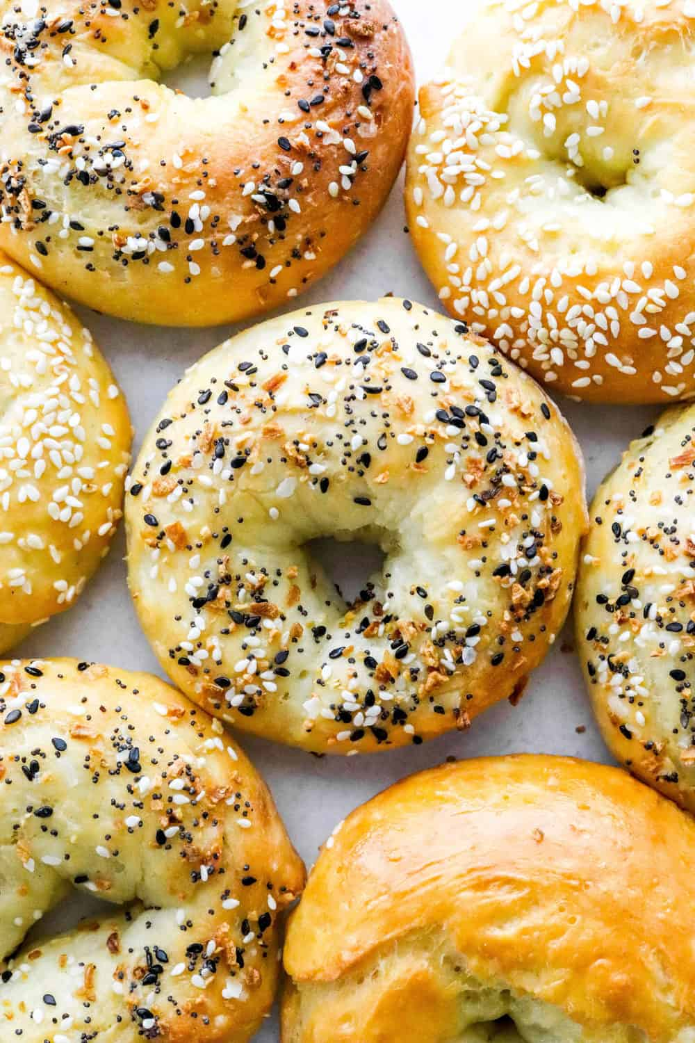 Homemade bagels with everything seasoning on them spread out on a white surface