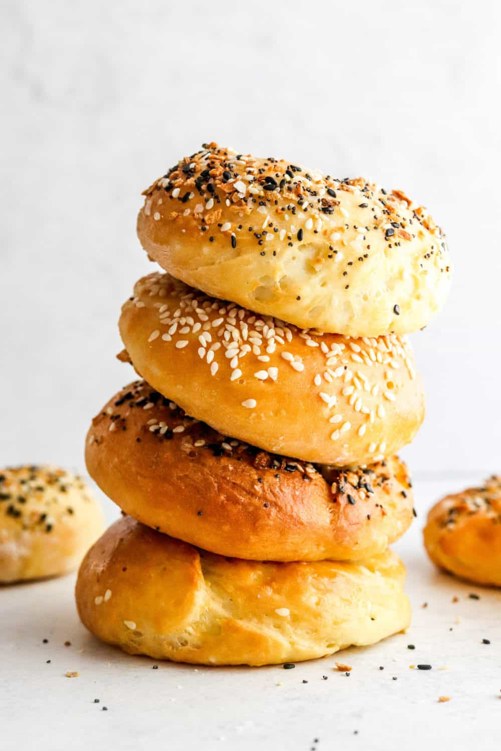 Stack of gluten free bagels with seasoning on some of them with a few more behind them.