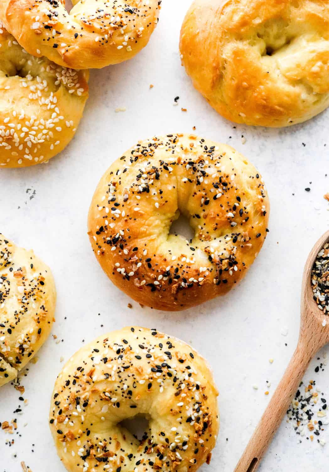 Round air Freyr bagel on a white surface surrounded by more bagels with a spoon of seasoning nest to them