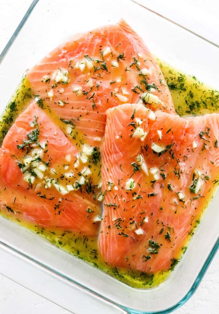 Raw salmon filets in a glass dish covered in a yellow and green dressing