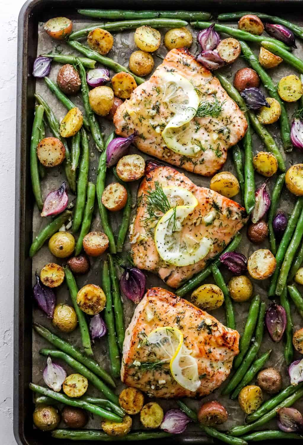Sheet pan salmon on a baking sheet with green beans, sliced potatoes and purple onion around the salmon.