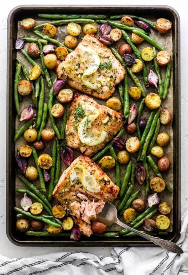Cooked salmon filets, surrounded by cooked green beans, purple baby onion and baby potatoes spread around the salmon on a sheet pan