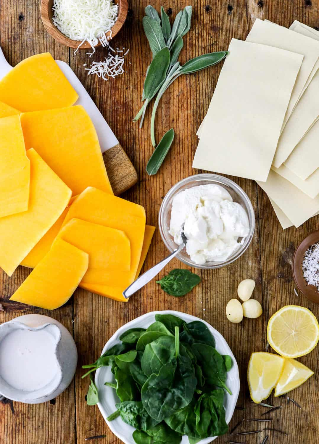 Sliced planks of butternut squash on a wooden board next to fresh sage leaves, bowl of shredded mozzarella, lasagna noodles, bowl of ricotta cheese, plate of spinach, cut lemons and jar of milk all spread out on a wooden board.