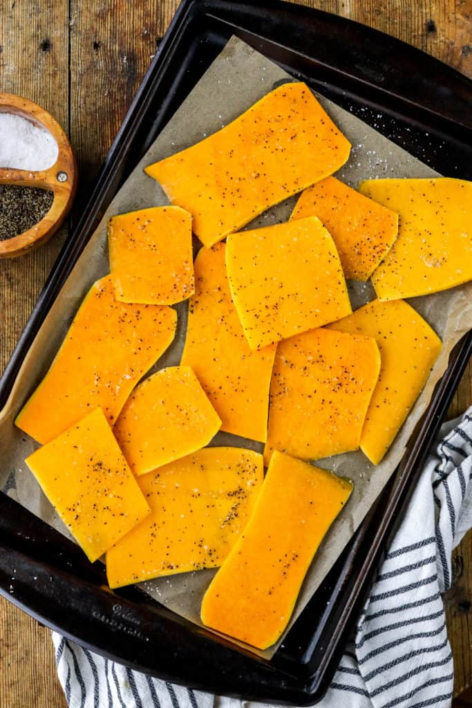 Planks of butternut squash on a brown baking sheet with a wooden container of salt and pepper next to it.