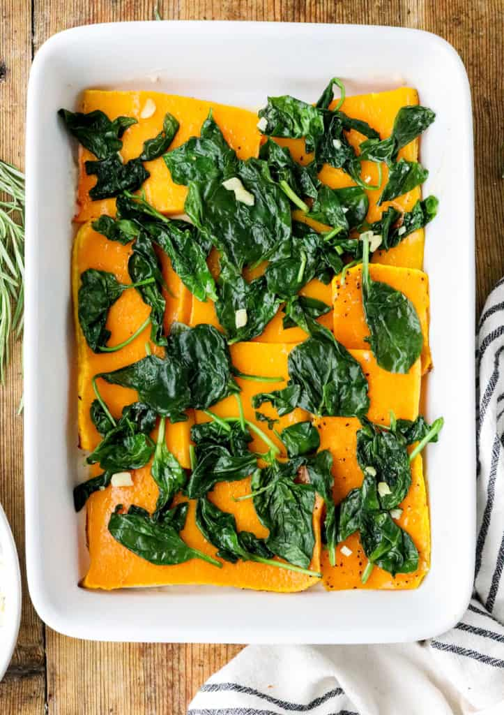 Baking dish filled with roasted pieces of butternut squash topped with cooked spinach