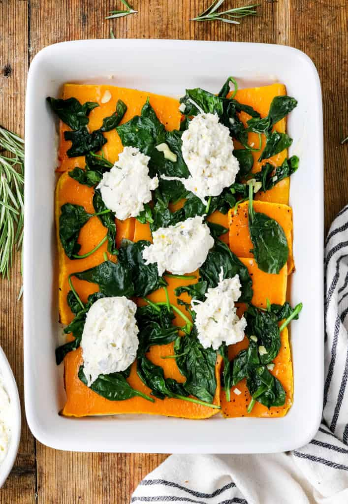 White baking dish with squash, spinach and cheese in it.