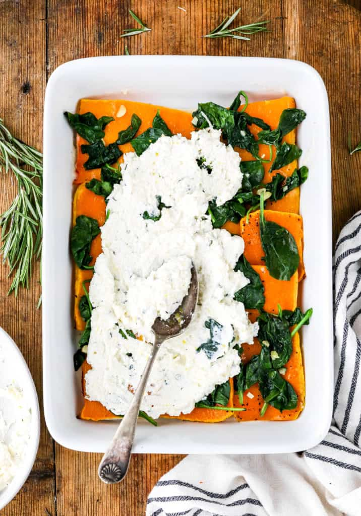 Spoon spreading cheese over some spinach and squash in a rectangle baking dish on top of a wooden surface