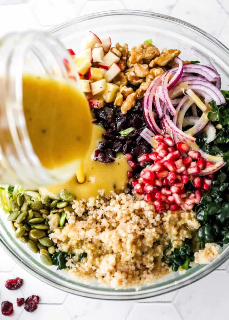 Pouring yellow dressing over a kale and quinoa salad with pomegranate seeds and sliced red onion on it.