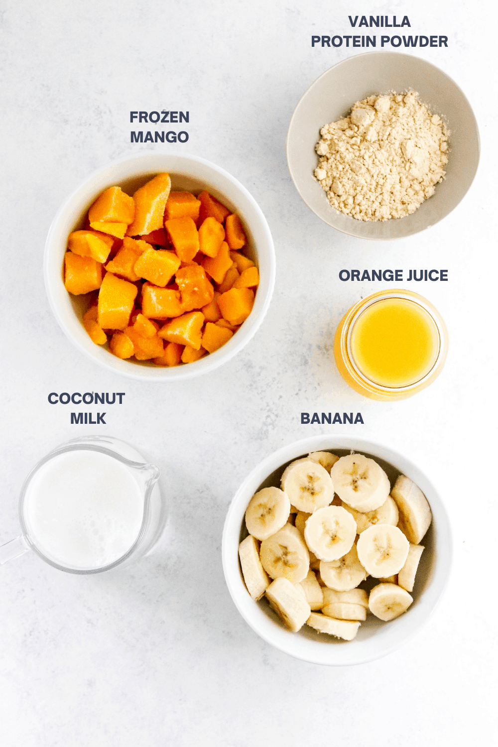 Round bowl filled with white protein powder with a bowl of chopped mango, a glass of orange juice, a glass of milk and a white bowl filled with sliced banana in front of it.