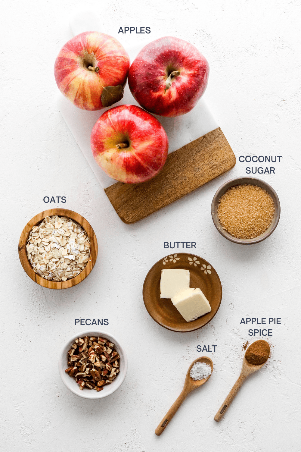3 whole red apples on a cutting boar with a bowl of sugar, bowl of oats, brown small plate with a couple cubes of butter, bowl of pecans, wooden spoon with salt and another wooden spoon with apple pie spice in front of it.
