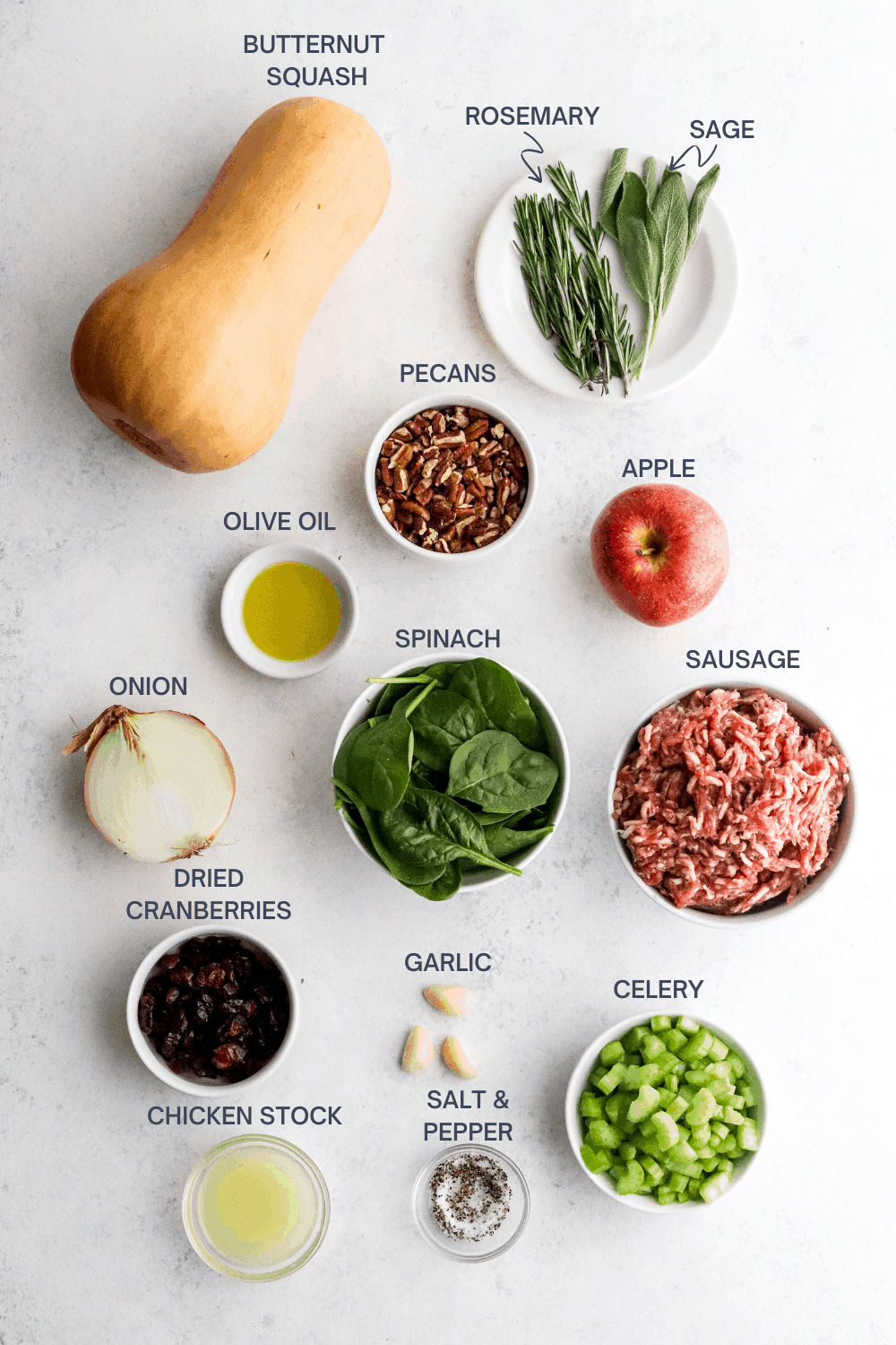 Whole butternut squash with fresh herbs next to it and an apple, bowl of pecans, bowl of olive oil, bowl of spinach, bowl of raw sausage, garlic cloves, bowl if diced celery, bowl if dried cranberries and a bowl of salt and pepper in front of it on a white surface.