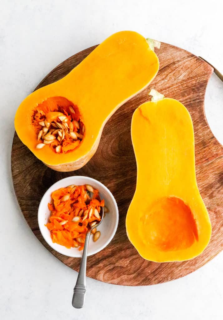 Two halves of butternut squash on a round wooden board on a white surface with a round white bowl  with seeds of of the squash and a spoon in it on the board next to the squash.