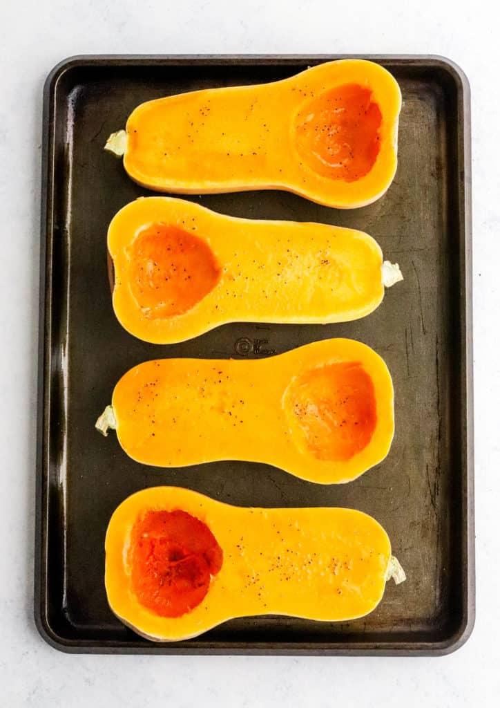 4 halves of butternut squash on a brown baking sheet.