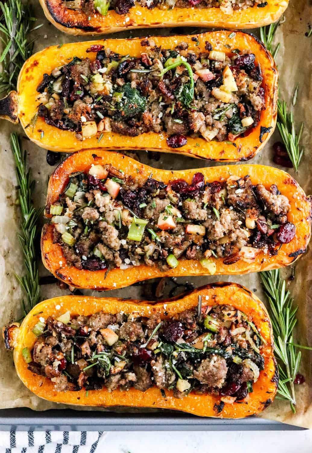 4 stuffed butternut squash halves filled with sausage, apples an fresh herbs on a baking sheet on top of brown parchment paper.