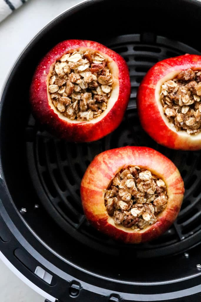 Air fryer basket with 3 whole apples stuffed with oat and nuts filling